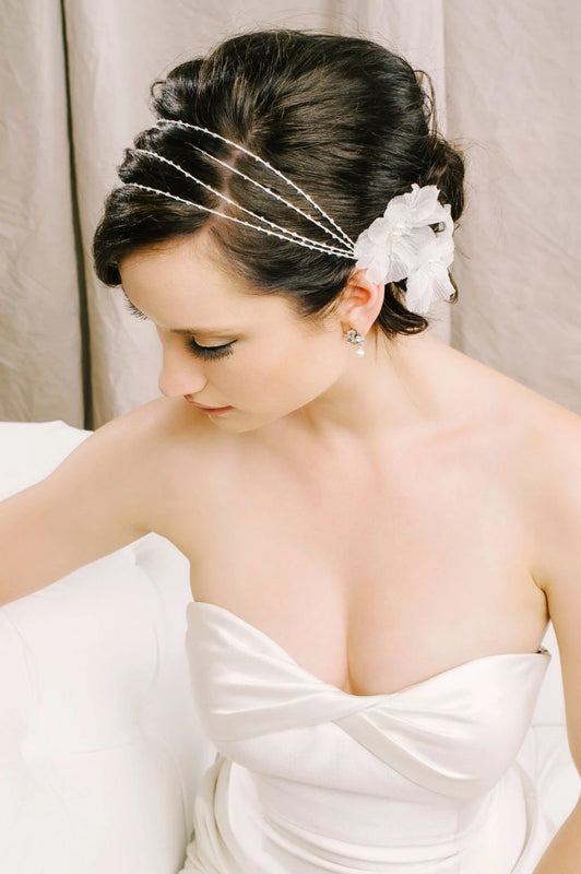 A bride in her wedding dress, gazing down and to the right, wearing her delicate hair wrap made with freshwater pearls, small clear Swarovski crystals and silk flowers alongside her sparkling single drop earrings. Sara Gabriel
