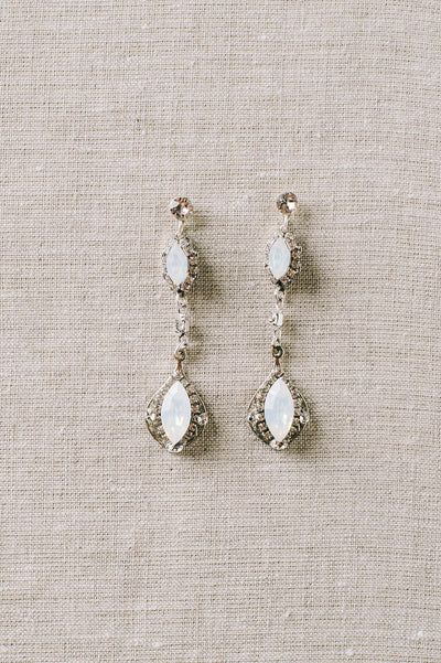 A pair of multi-drop stiletto earrings that use a mixture of clear and opal Swarovski crystals all dangling from a crystal post. Sara Gabriel.