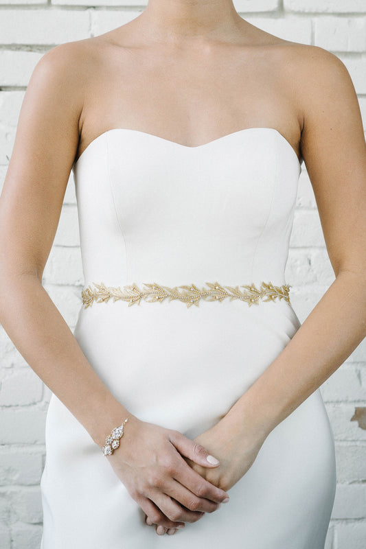 A vine-like, hand-stitched gold colored embroidered duet that has a soft tulle edge and clear Swarovski crystal-set chain. The duet is tied around the waste of a bride. Sara Gabriel.