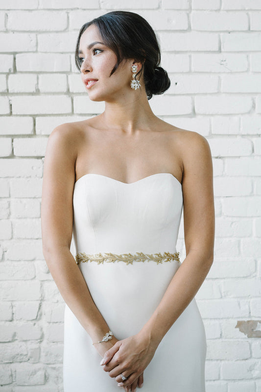 Looking away, a bride is wearing a white wedding dress and bridal accessories. Tied around her waist is a gold hand-stitched and embroidered duet that incorporates a delicate vine-like design that uses Swarovski crystal set-chain and soft tulle. Sara Gabriel.