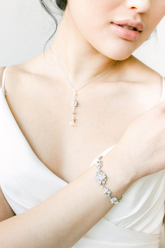 A bride displaying a teardrop pendant necklace and a glittering bracelet. The bracelet features dozens of hand-set clear Swarovski crystals. Made by Sara Gabriel.