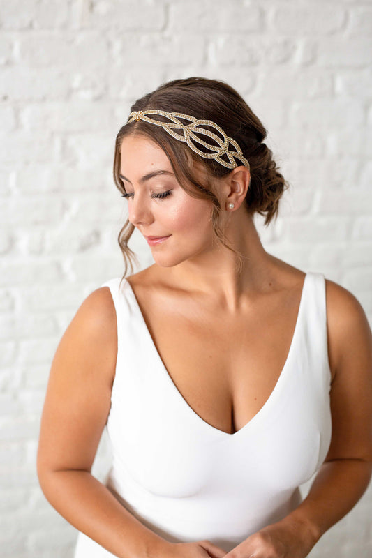 A bride in a white wedding dress looking to her right, wearing a hand-embroidered duet that features gold plated crystal-set chain in her hair. Sara Gabriel