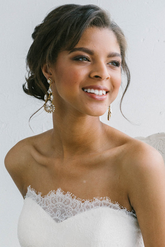 A bride is wearing a white lace wedding dress and a pair of intricate chandelier earring that is hand-set with clear and opal Swarovski crystals. Sara Gabriel.