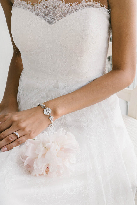 A bride is wearing a lace wedding dress and a bracelet around her wrist. The bracelet is art deco-inspired. It features multiple segments each of varying sizes. They are made with clear Swarovski crystals. Sara Gabriel.