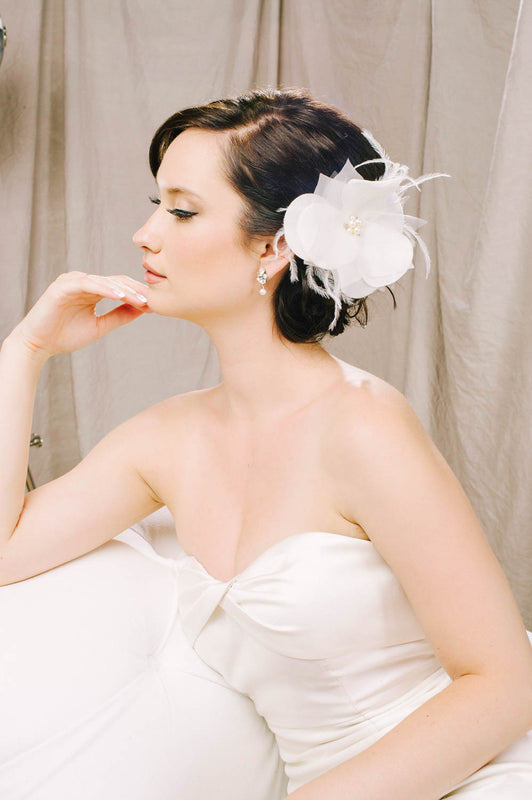 A bride in her wedding dress turned to the right, looking ahead. With her hand to her chin, she is wearing a silk velvet organza and tulle petal hair clip. The fluttering flower-shaped clip features clusters of Swarovski crystals and freshwater pearls in the center. Soft feathers are also a feature of this clip. Sara Gabriel