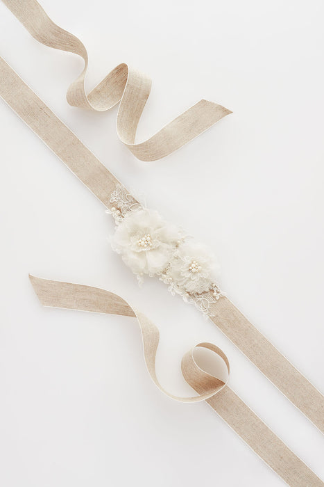 A sash that features hand-cut Alençon lace layers and hand-pressed silk petals on french linen. The flowers incorporate Swarovski crystals and imitation ivory. Sara Gabriel