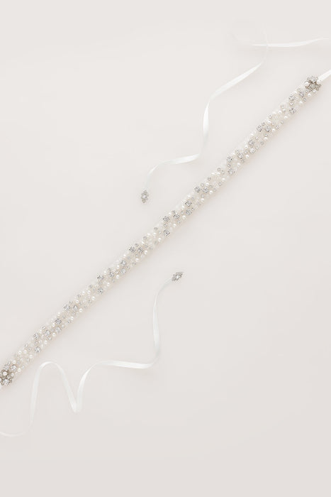 A bridal duet laid against a white background. The duet consists of clear Swarovski crystals and diamond white pearls. On each of duet is a diamond white piece of ribbon. Sara Gabriel