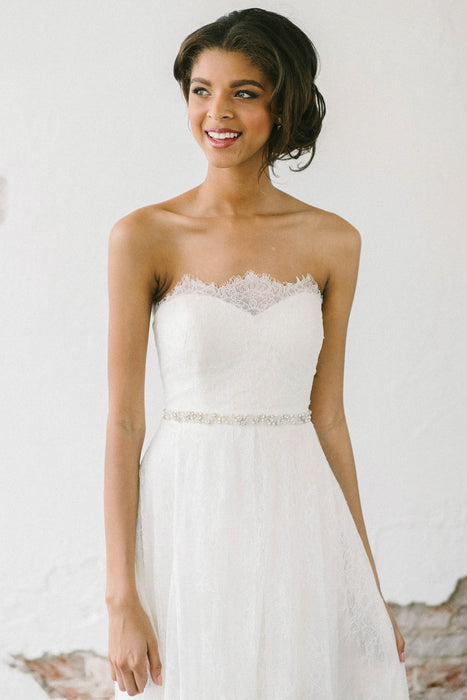 A smiling bride wearing a white lace wedding dress. Around her waist is a hand-stitched and embroidered piece that uses dozens of Swarovski clear crystals and pale ivory pearls sewn onto sheer netting. Sara Gabriel