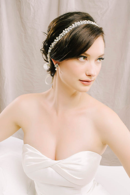 A bride gazing to her left sitting down on a white couch. In her hair, she is wearing a duet that is hand-stitched with Swarovski clear crystals and pale ivory pearls. Sara Gabriel