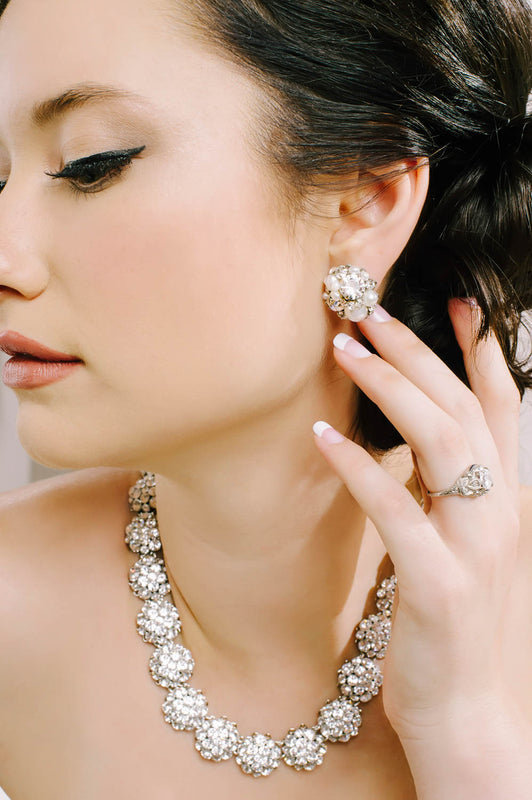 A woman showcasing her dome-shaped stud earrings that include clusters of clear Swarovski crystals and pearls. She is also wearing a dome-shaped designed necklace. It is made with clear Swarovski crystals. Sara Gabriel.