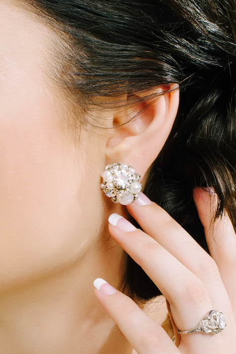 A closeup of a vintage-inspired stud earring being worn. The earring is dome-shaped and hand-set with clear Swarovski crystals and pearls. Sara Gabriel