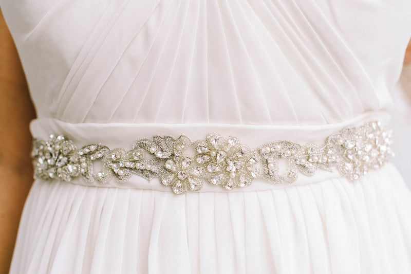 A closeup of a bridal accessory being worn around a waist. The pattern is inspired by French lace and is a floral-like design. Made with Swarovski crystals and pearls. Sara Gabriel