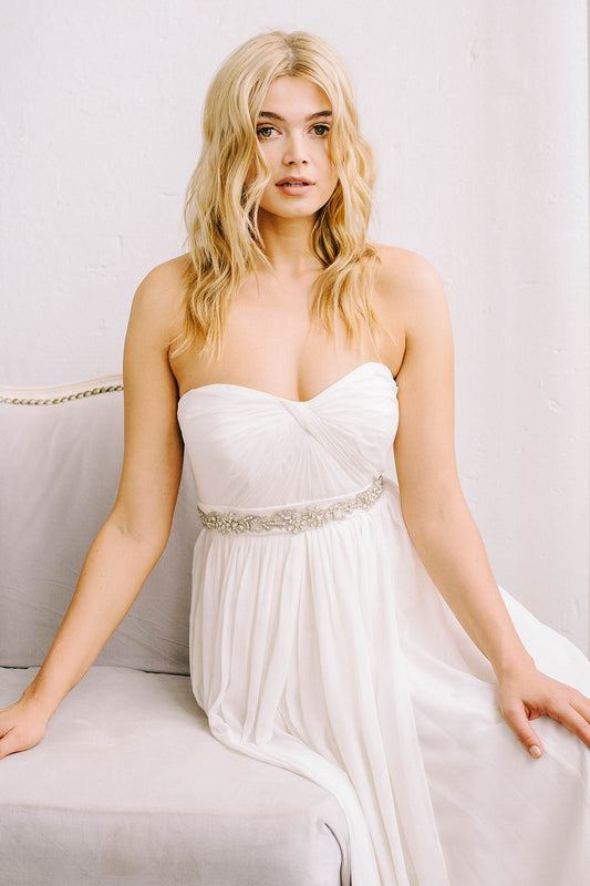 A bride sitting on a beige couch and wearing a white wedding dress. She is looking into the camera. Around her waist is bridal accessory that is inspired by French lace. It is hand-stitched into a floral-like design and uses Swarovski crystals and pearls. Sara Gabriel