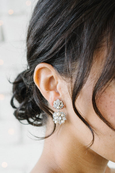 A woman with only the side of her face visible is wearing a drop earring. The earring is vintage-inspired and features a mix of Swarovski clear crystals and pale ivory pearls. Sara Gabriel