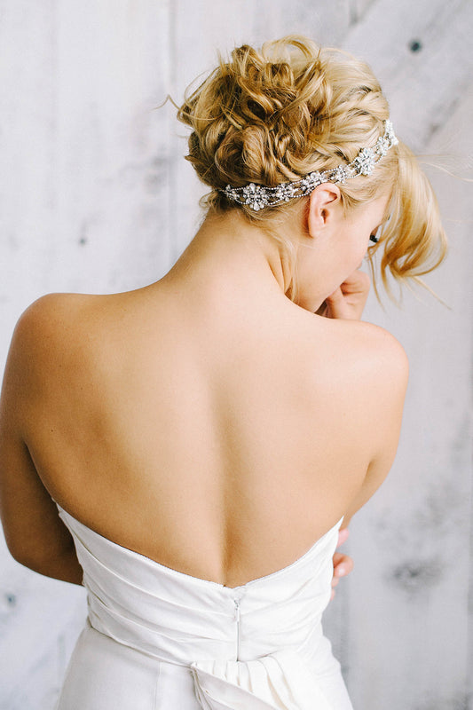 A bride with her back turned wearing a white wedding dress and a halo in her hair. The halo is made made with Swarovski crystal and pearl encrusted filigrees that are each interwoven with crystal-set chain. Sara Gabriel