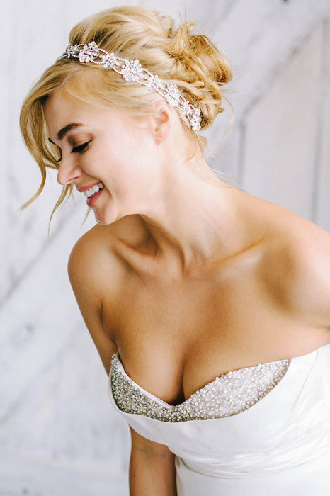 A smiling bride who is wearing a beaded white wedding dress and looking down to her right. She is wearing a halo that is resting on hair. The halo consists of Swarovski crystal and pearl encrusted filigrees that are interwoven with crystal-set chain. Sara Gabriel