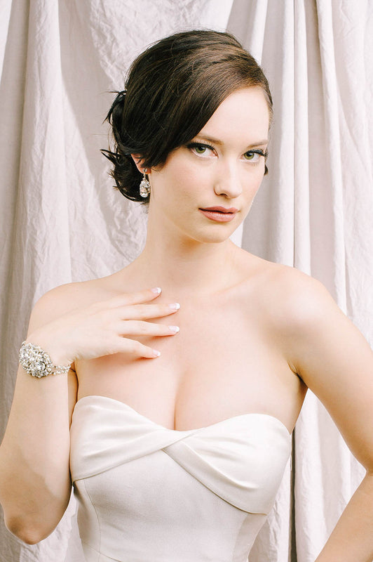 A woman in a wedding dress gazing into the camera. She has her hand up to her chest, showcasing her oval-shaped statement bracelet. The bracelet consists of caviar-style beading that is made with Swarovski clear crystals and pale ivory pearls. Sara Gabriel