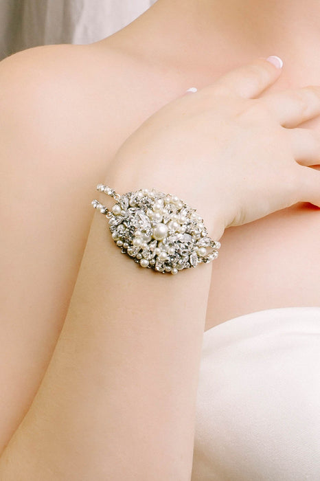 A closeup of a bracelet being worn. The bracelet consists of an oval-shaped metal filigree as its centerpiece. The caviar-style beading consists of Swarovski clear crystals and pale ivory pearls of various size. The bracelet is connected by double strands of crystal and pearl-set chain. Sara Gabriel