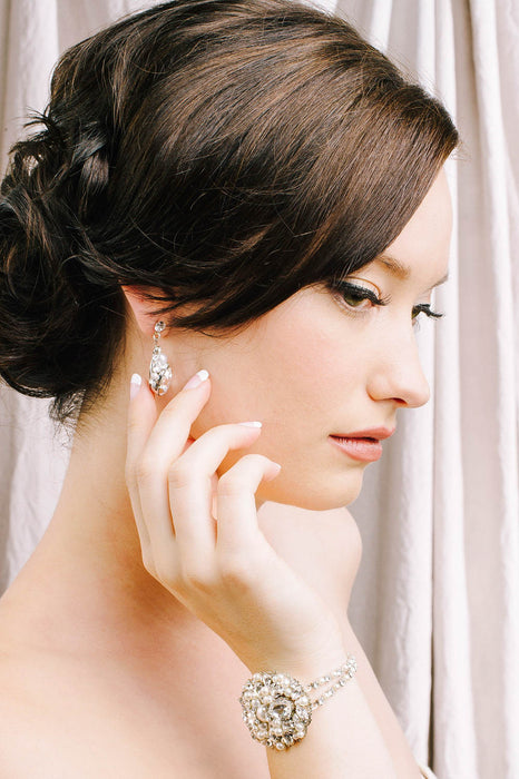 A woman facing to the side, touching her earring that is dangling from her right ear. On her wrist is an oval-shaped bracelet that is connected by double strands of crystal and pearl-set chain on each side. The oval metal filigree is encrusted caviar-style with clear Swarovski crystals and pale ivory pearls. Sara Gabriel