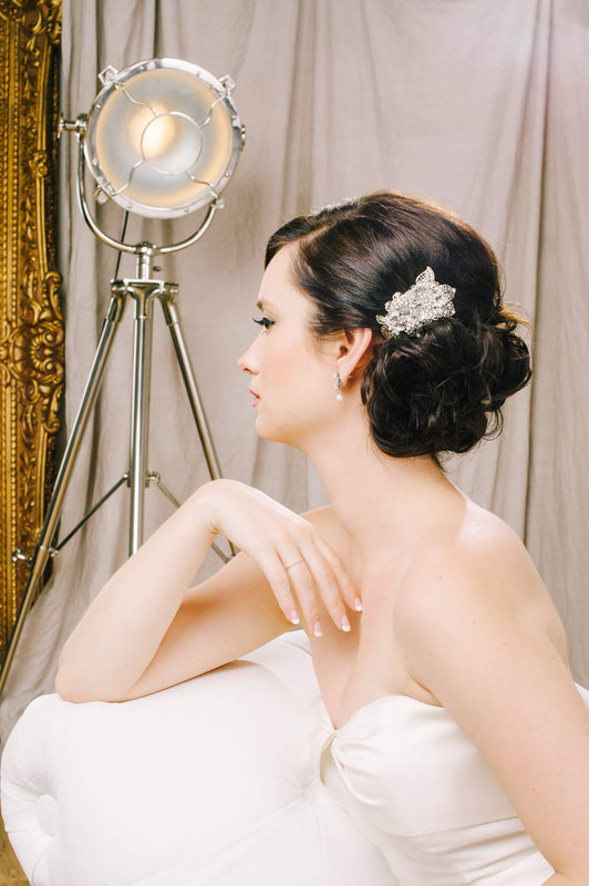 A bride in her wedding dress, sitting on a couch turned to the side. She is wearing a hair clip that features filigree metalwork and hand-set with Swarovski crystals and pearls. Sara Gabriel