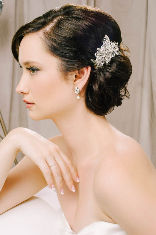 A bride sitting, with her body turned to the side showing that she is wearing a hair clip. The hair clip is a vintage-inspired clip that features filigree metalwork that is hand-set with Swarovski crystals and pearls. Sara Gabriel