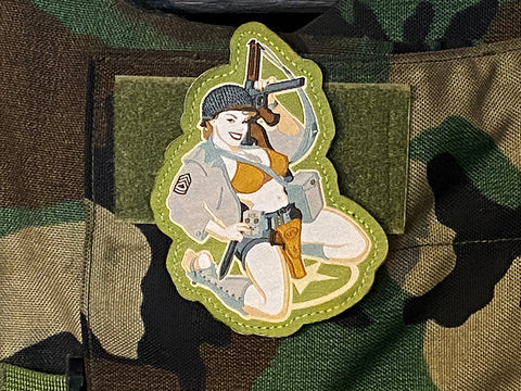 Pinup girl patch: a retro tactical pinup with Thompson gun on woodland camo body armor