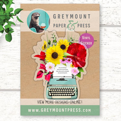 Clear vinyl stickers with a vintage typewriter design with flowers bursting from the page. Vintage typewriter laptop sticker.