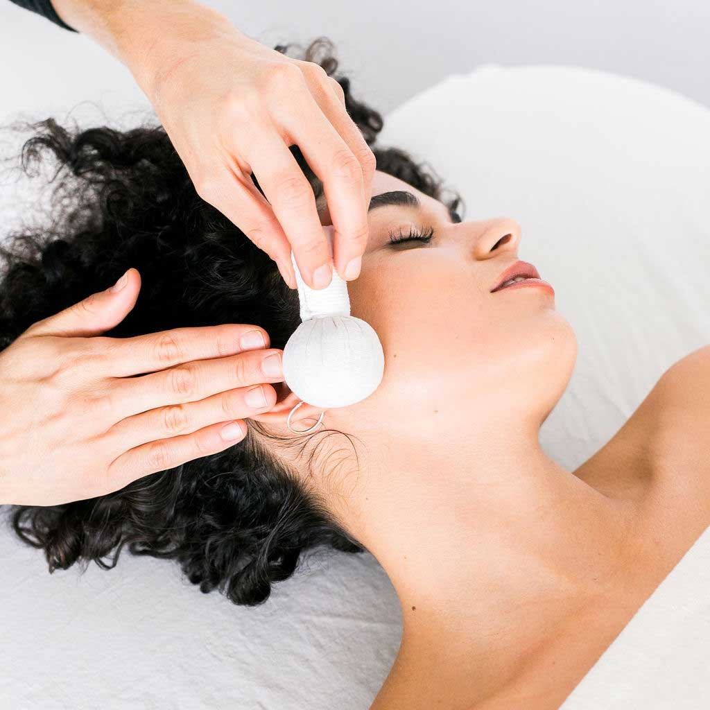Women receiving herbal poultice treatment