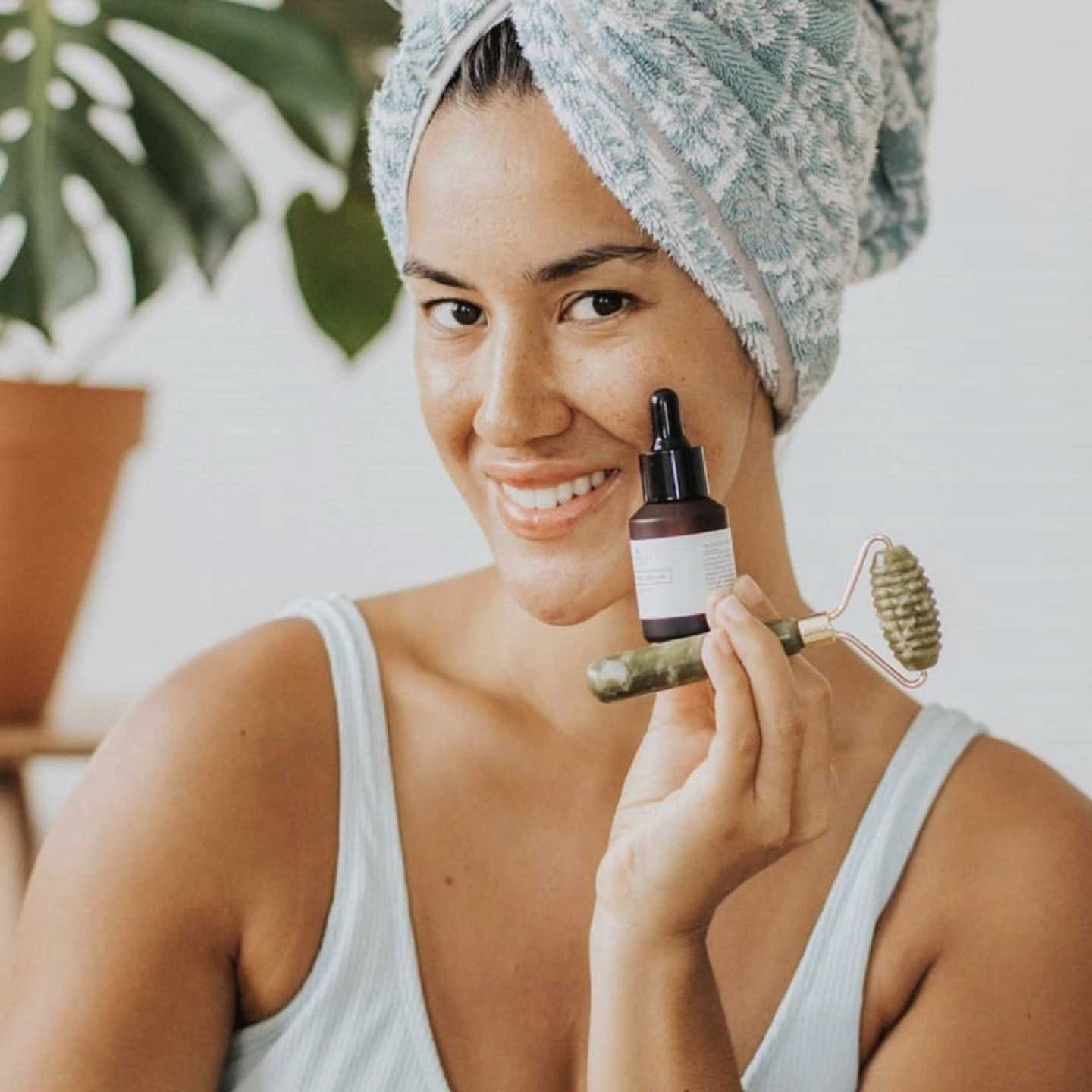 Woman holding Primally Pure Clarifying Serum and Green Jade Roller