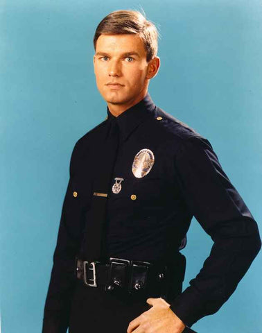 Adam-12 Man in Police Uniform Making Serious Face in Blue Background High Quality Photo