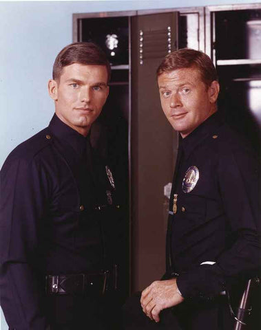 Adam-12 Posed in Police Uniform Looking at the Camera Near the Shelf in a Portrait High Quality Photo