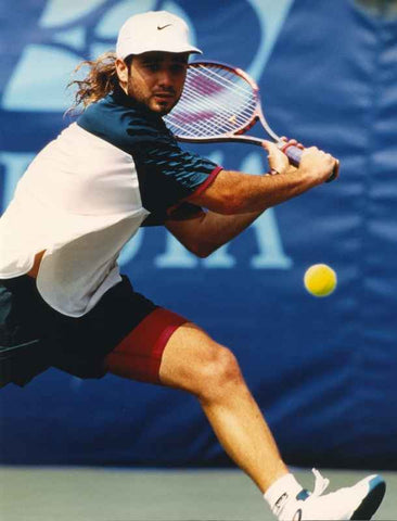 Andre Agassi Reaching a Ball and Hitting with a Back Hand on a Tennis Match High Quality Photo