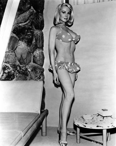 Joi Lansing standing and wearing a Polka Dot Bikini Near the Couch in a Portrait High Quality Photo