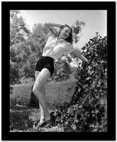 Vera Zorina leaning backwards with an outstretched arm on a vine covered rock, wearing shorts, and a button down, short-sleeved shirt.