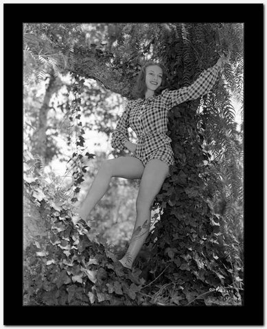 Vera Zorina smiling broadly, standing in tree, wearing a checkered, long-sleeve romper.