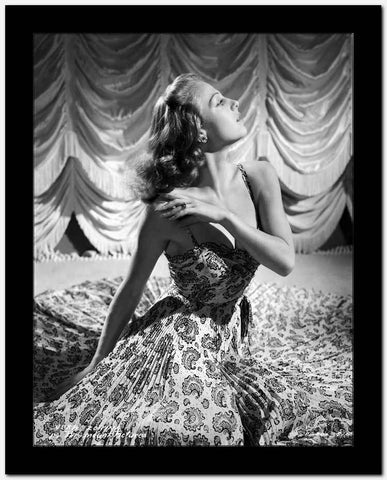 Vera Zorina photographed wearing a paisley print, strapless dress, spilled around her while sitting on the floor.