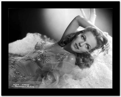 Vera Zorina laying on white, plush blankets, wearing a sweetheart, sleeveless dress, with tule overlay, beautifully decorated with amzing patterns sewn with sequins.