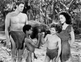 Johnny Weissmuller standing with Two Kids and a Woman in a Movie Scene Premium Art Print