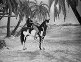 Johnny Weissmuller Riding a Black and White Horse in a Classic Movie Scene Premium Art Print