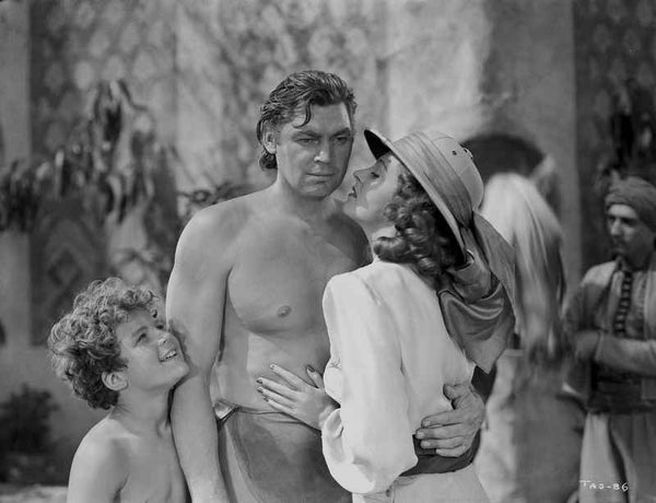 Johnny Weissmuller Receiving a Kiss from a City Girl in a Classic Movie Scene Premium Art Print