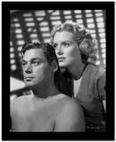 Johnny Weissmuller sitting with a Woman standing in His Back in a Classic Movie Scene High Quality Photo