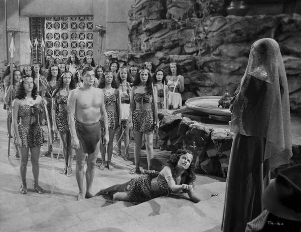 Johnny Weissmuller standing in Front of the Leader of the Amazons in a Movie Scene Premium Art Print