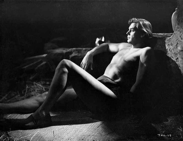 Johnny Weissmuller Lying on the Floor and Leaning on a Rock in a Classic Movie Scene Premium Art Print