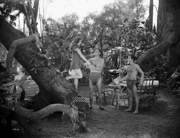 Johnny Weissmuller Helping a Woman to Get Down the Tree in a Movie Scene Premium Art Print