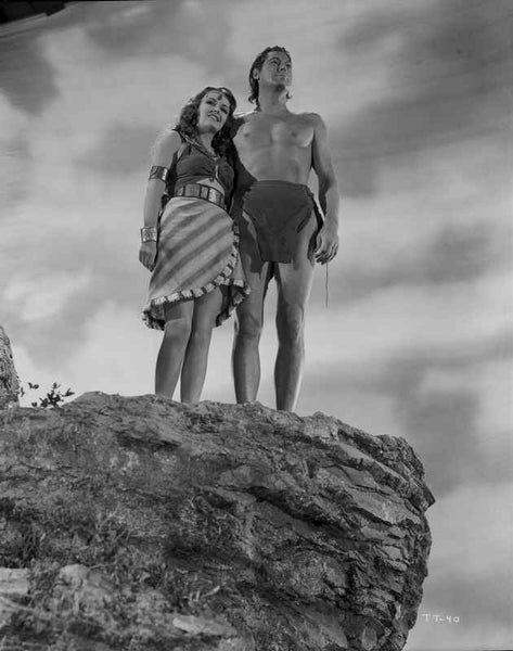 Johnny Weissmuller standing on a Cliff with a Woman in a Movie Scene Premium Art Print