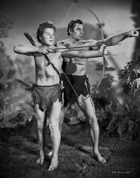 Johnny Weissmuller Leading a Young Man to Shoot His Arrow in a Classic Movie Scene Premium Art Print