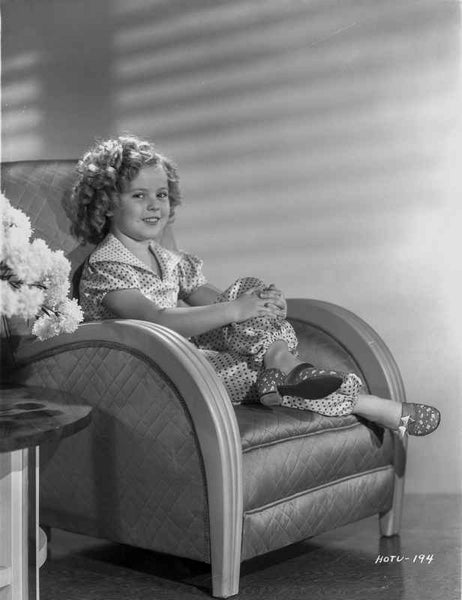 Shirley Temple sitting on the Couch while smiling Premium Art Print