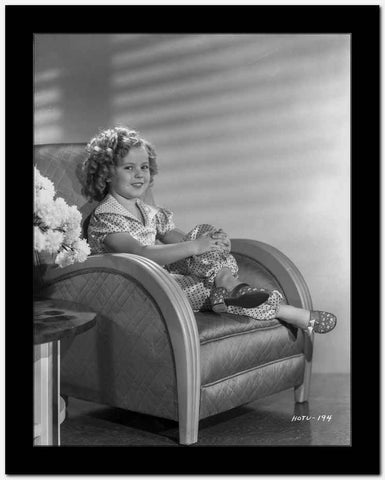 Shirley Temple sitting on the Couch while smiling High Quality Photo