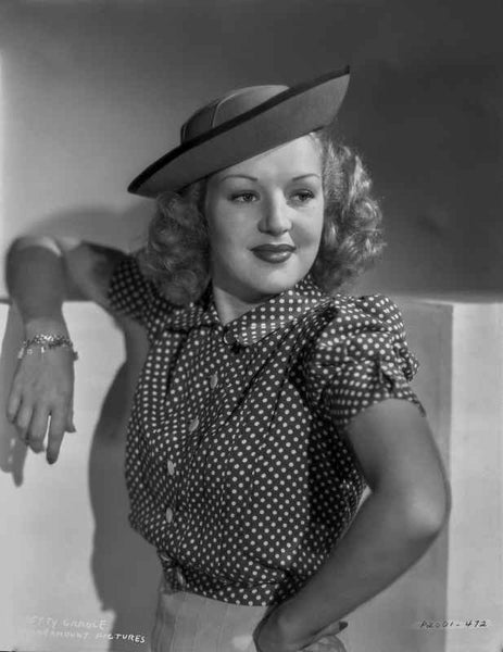 Betty Grable Posed with Hand on the Waist in Black Polka Dot Dress and White Skirt with Round Hat Premium Art Print