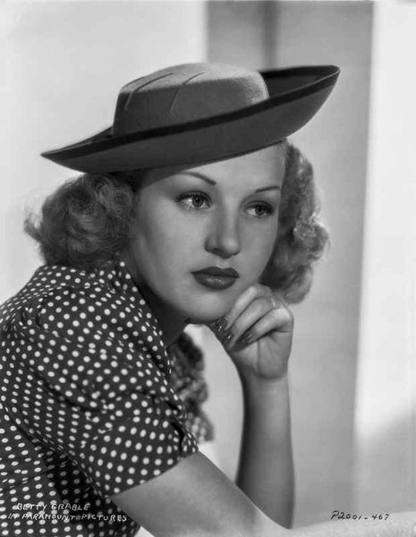 Betty Grable Portrait with Chin Leaning on Hand in Velvet Hat and Polka Dot Short Sleeve Dress Premium Art Print